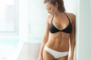 Fit woman in white and black underwear with toned abs